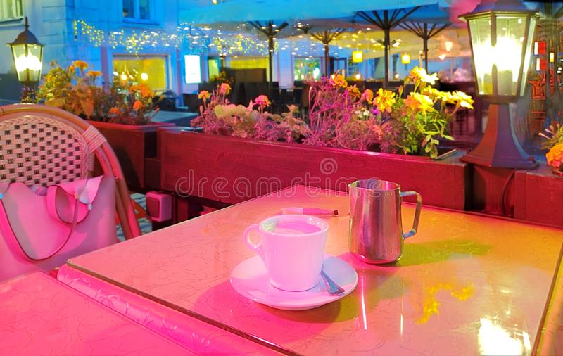 Summer night Street cafe  bokeh blurring city light evening restaurant table cup of coffee on top view candle lamp  light reflecti. On on glass  summer night new royalty free stock photography