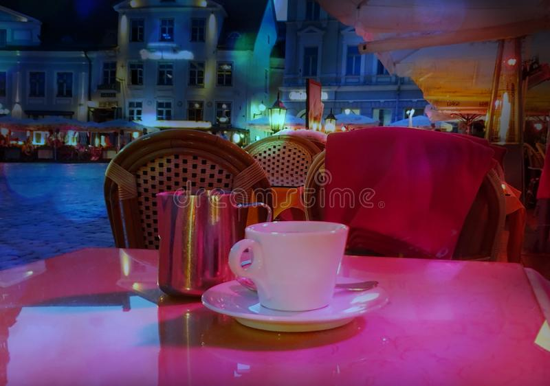 Summer night Street cafe  bokeh blurring city light evening restaurant table cup of coffee on top view candle lamp  light reflecti. On on glass  summer night new stock images