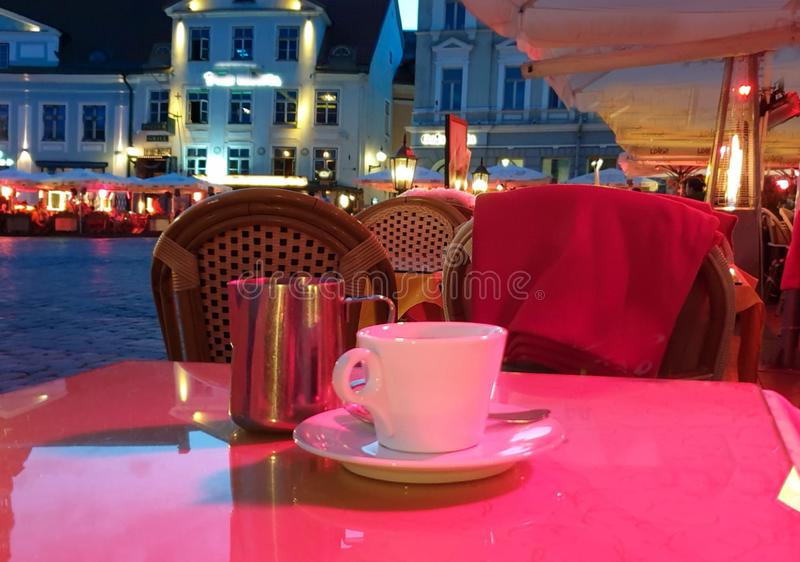 Summer night Street cafe  bokeh blurring city light evening restaurant table cup of coffee on top view candle lamp  light reflecti. On on glass  summer night new royalty free stock photo