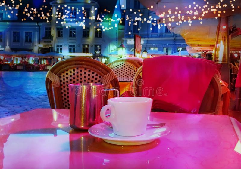 Summer night Street cafe  bokeh blurring city light evening restaurant table cup of coffee on top view candle lamp  light reflecti. On on glass  summer night new stock photos