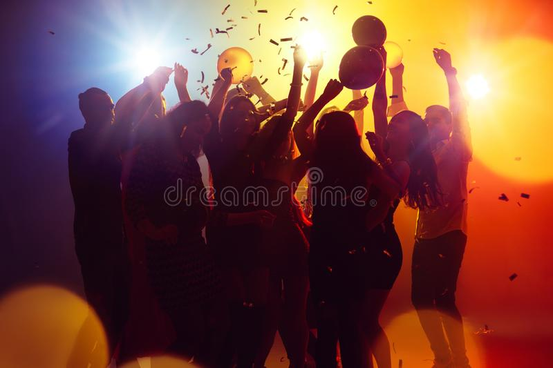 A crowd of people in silhouette raises their hands against colorful neon light on party background. Summer nights. A crowd of people in silhouette raises their royalty free stock image