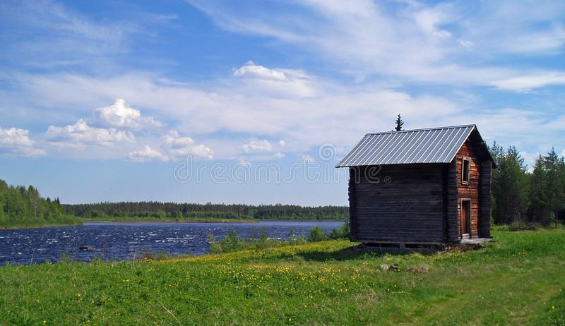 Summer in the north. Sweden Tornedalen water river clouds loghouse building royalty free stock image