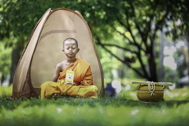 Summer novices are meditating. BANGKOK, THAILAND – APRIL 8: A small summer novice who is meditating on the outdoor with green nature surrounding on April stock photo