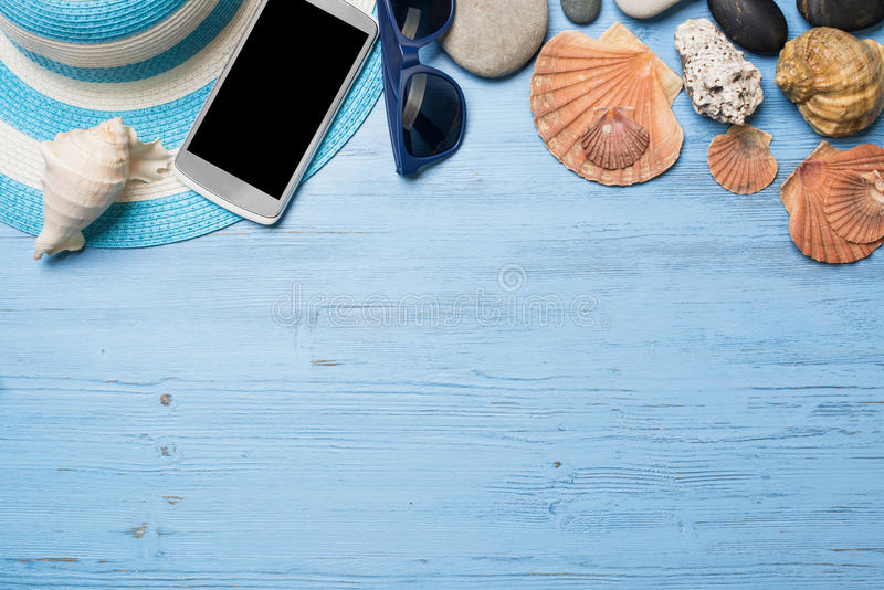 Summer objects for vacation. Straw hat sunglasses smartphone among sea shells and stones on wooden surface stock images