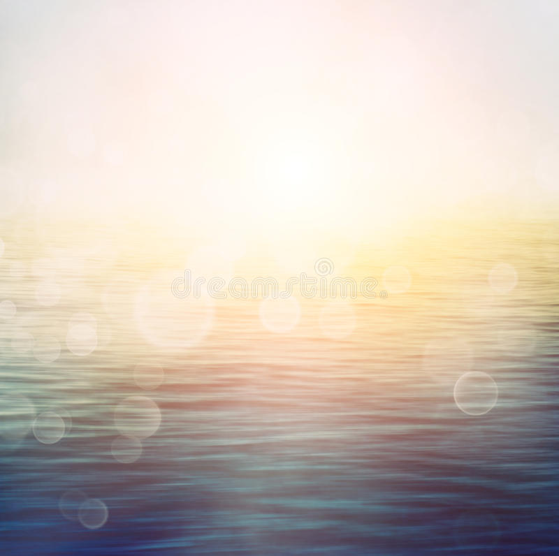 Summer ocean. Abstract nature summer or spring ocean sea background. Small waves on water surface in motion blur with bokeh lights from sunrise