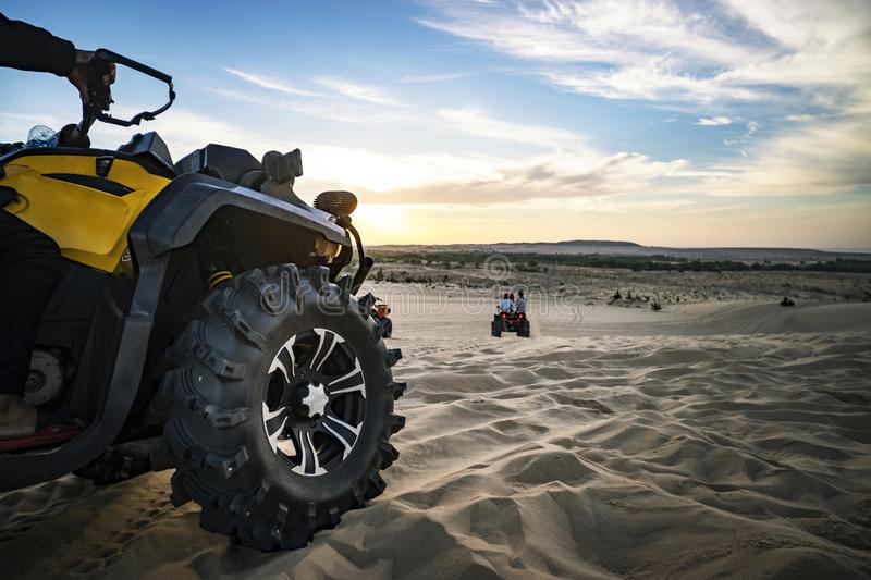 Summer offroad adventure on atv in sand quarry. Entertainment of tourists in desert in MUI ne in Vietnam. Off-road ATV wheel close. Summer offroad adventure on stock image