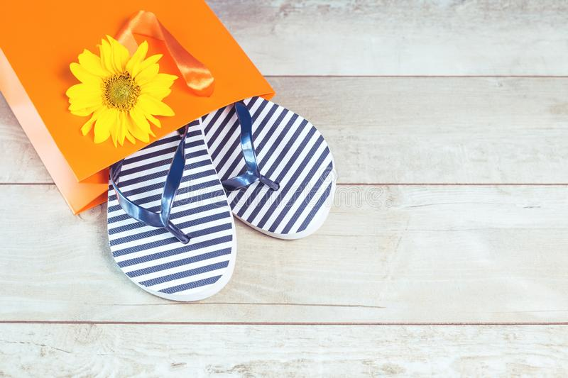 Summer orange bag and flip flops on wooden background stock photography