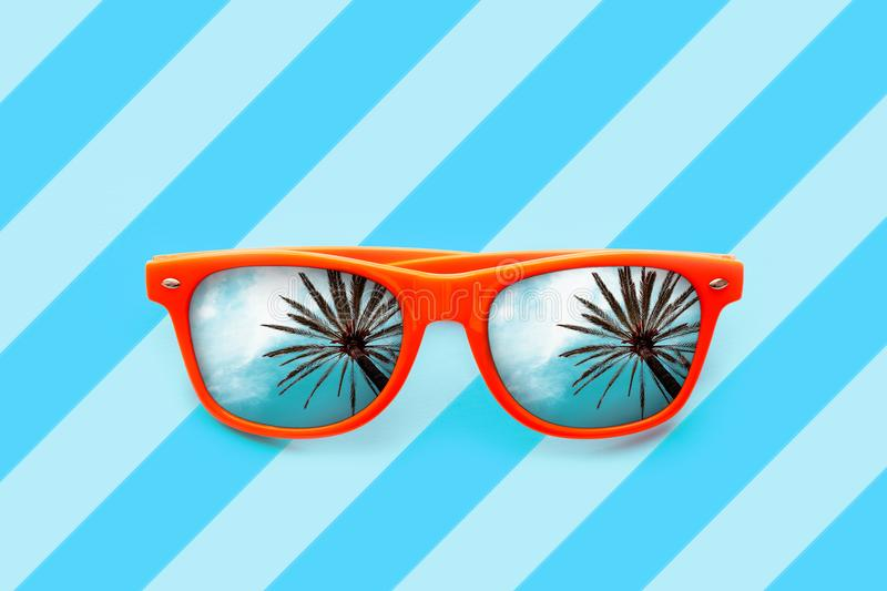 Summer orange sunglasses with palm trees reflections isolated in blue background with diagonal stripes. Minimal concept for summer holidays, sun protection royalty free stock photo