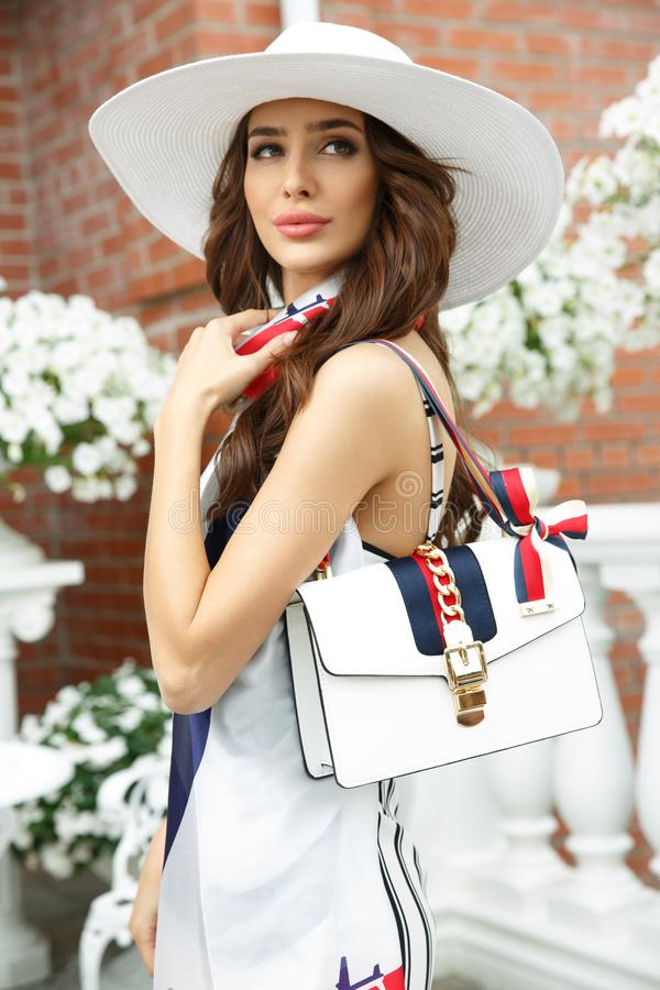 Summer outdoor photo of beautiful, attractive and elegant rich young lady in hat with stylish accessories royalty free stock images