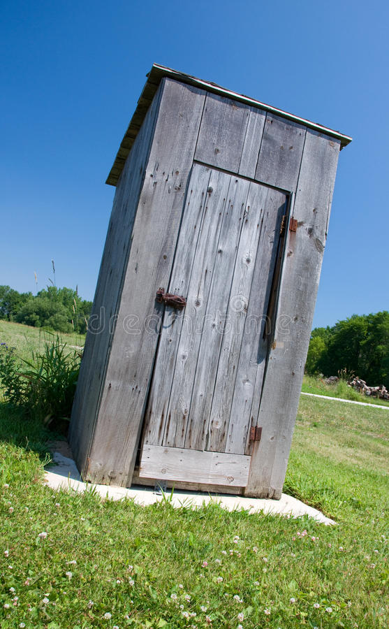 Summer Outhouse. Photograph of an old outhouse against a summer sky in a midwestern park stock photo