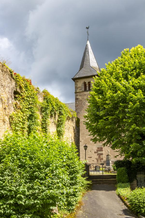 Summer overcast view of the main entrance to the Church of St. Peter in Roth an der Our, Germany, the church tower in the stock photo