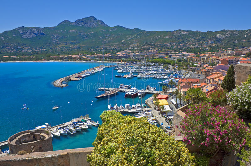 Summer panorama of Calvi, Corsica. Panorama of Calvi from the citadel with the old tower, pleasure boats, and mountains, Corsica, France stock photo