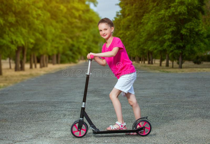 In the summer in the park the girl is riding a scooter stock image