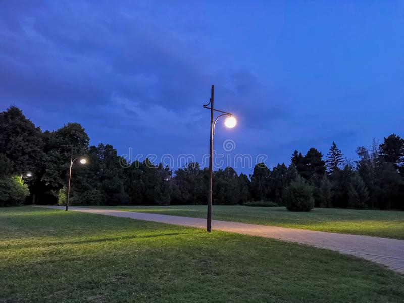 Summer park, Russia. Evening in the city Park. Lantern, trees, paths and lawn. in the background. Summer park, Russia. Wooden benches in an empty night park stock image