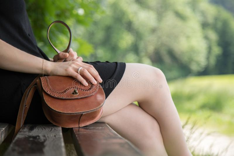 Summer in the park: Young woman in sexy black dress and ballerinas is sitting on a park bench. Young woman in black dress with sexy legs and leather handbag is royalty free stock photography