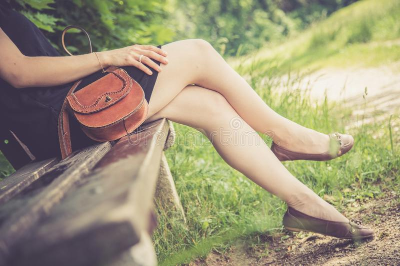Summer in the park: Young woman in sexy black dress and ballerinas is sitting on a park bench. Young woman in black dress with sexy legs and leather handbag is royalty free stock images