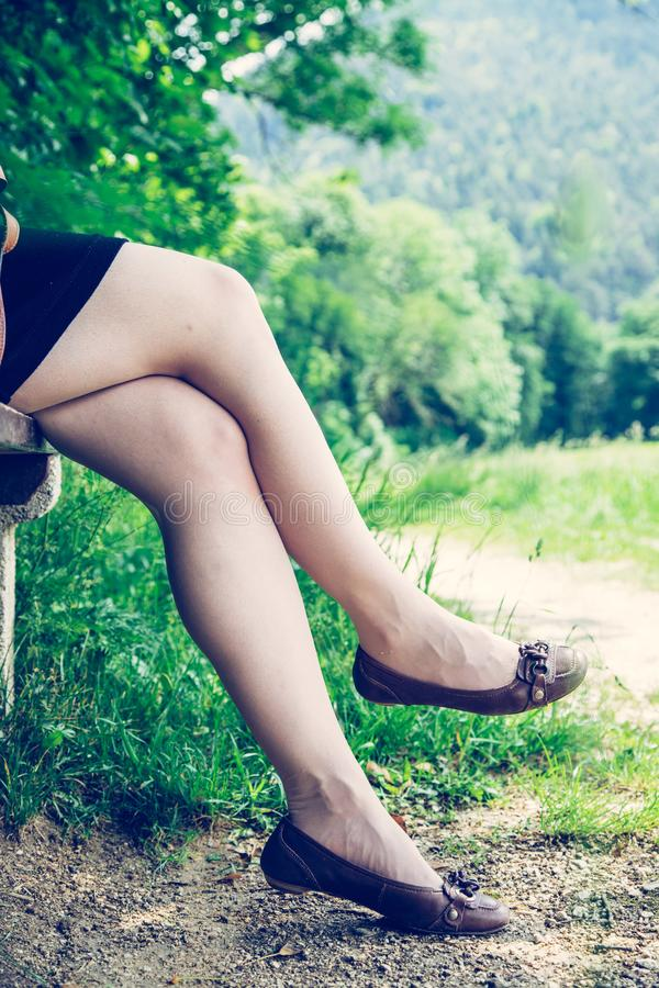 Summer in the park: Young woman in sexy black dress and ballerinas is sitting on a park bench. Young woman in black dress with sexy legs and leather handbag is stock photo