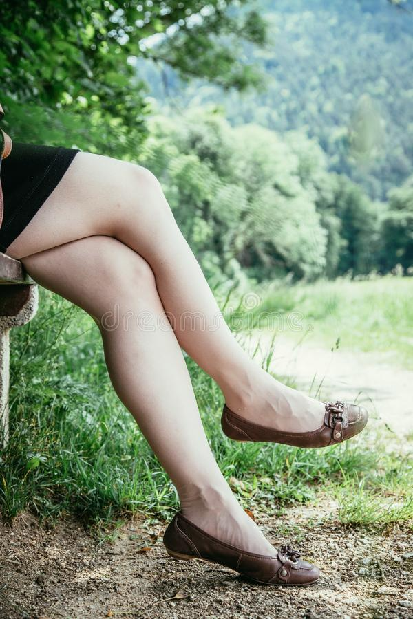 Summer in the park: Young woman in sexy black dress and ballerinas is sitting on a park bench. Young woman in black dress with sexy legs and leather handbag is stock photos