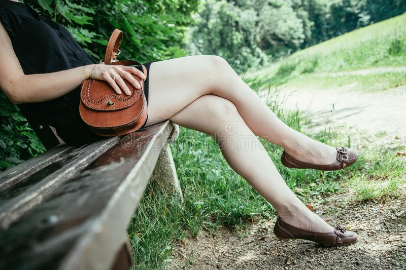 Summer in the park: Young woman in sexy black dress and ballerinas is sitting on a park bench. Young woman in black dress with sexy legs and leather handbag is stock images