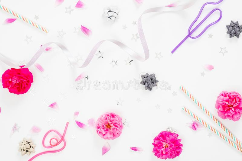 Summer party background with festive feminine accessories, ribbon, pink rose flower buds and petals on white background. Flat lay royalty free stock photo