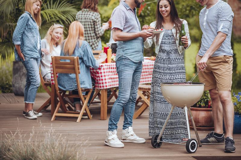 Summer party on patio. Group of colleagues having a summer party on a garden patio, sitting by a table and standing by a grill royalty free stock photo