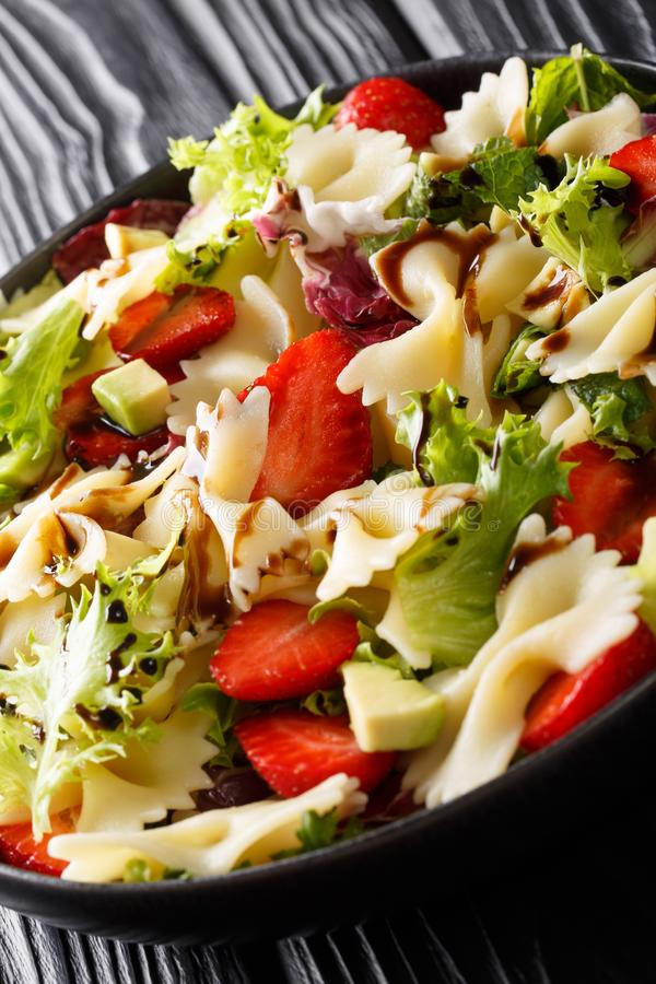 Summer pasta salad with avocado, strawberries, lettuce, dressed with balsamic sauce close-up on a plate. vertical stock image