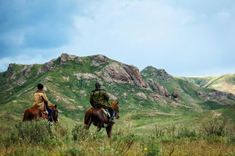 Summer pastures in an intermontane valley. Riders on horseback. Riders on horseback. Summer pastures in an intermontane valley. Kazakhstan royalty free stock image