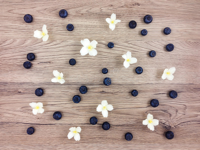 Summer pattern of jasmine flowers and berries on wooden table. Flat lay. Summer pattern of jasmine flowers and ripe blueberries on wooden table. Flat lay, top stock photo