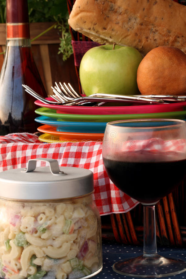 Summer Picnic. Wicker picnic basket full of fruit, bread and accessories. Pasta salad and wine bottle and glass on the sides. Red & white checked cloth in basket stock photography
