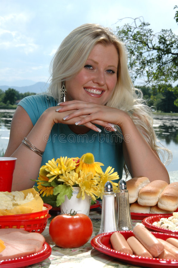 Summer Picnic. A beautiful blond woman sitting at a picnic table by a lake stock photography