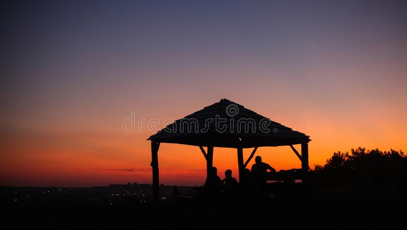 Summer picnic background with beautiful evening sky, pavilion and people silhouettes stock images