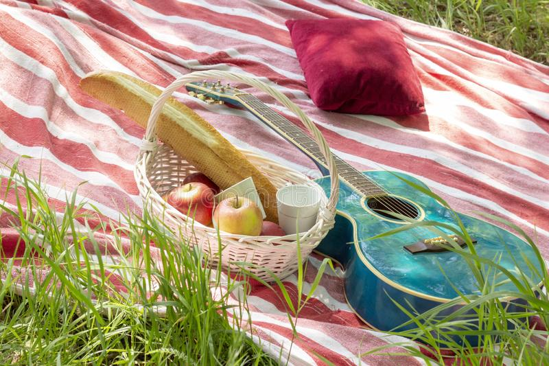 Summer picnic basket with apples and guitar lie on  plaid with pillows heat royalty free stock photo