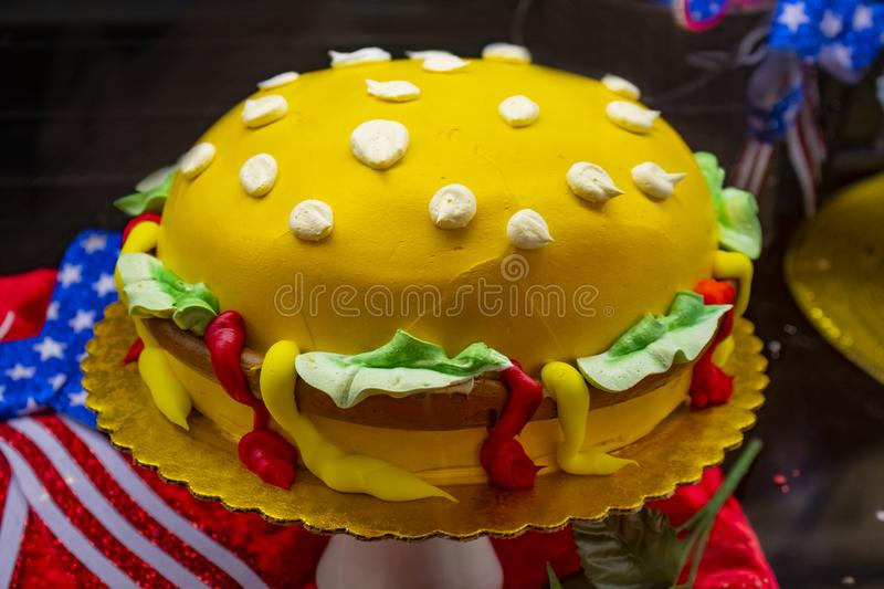 Summer picnic food - Cake decorated like a hamburger with red white and blue decorations in background - selective focus royalty free stock photography