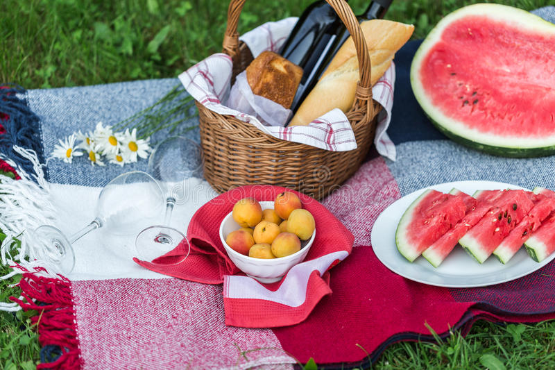 Summer picnic with French bread, wine and watermelon stock photography