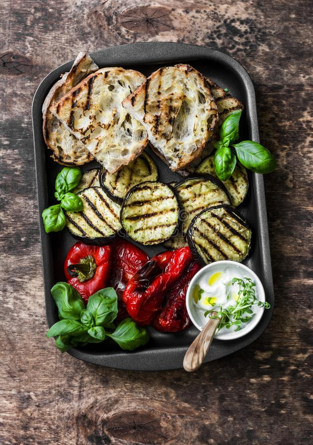 Summer picnic grilled vegetables - eggplant, bell peppers, ciabatta, yogurt sauce, basil in baking sheet on wooden background, top royalty free stock images