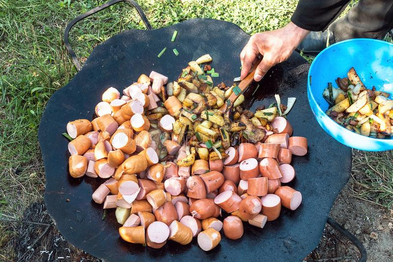 Summer picnic. Preparation of delicious sausages royalty free stock photography