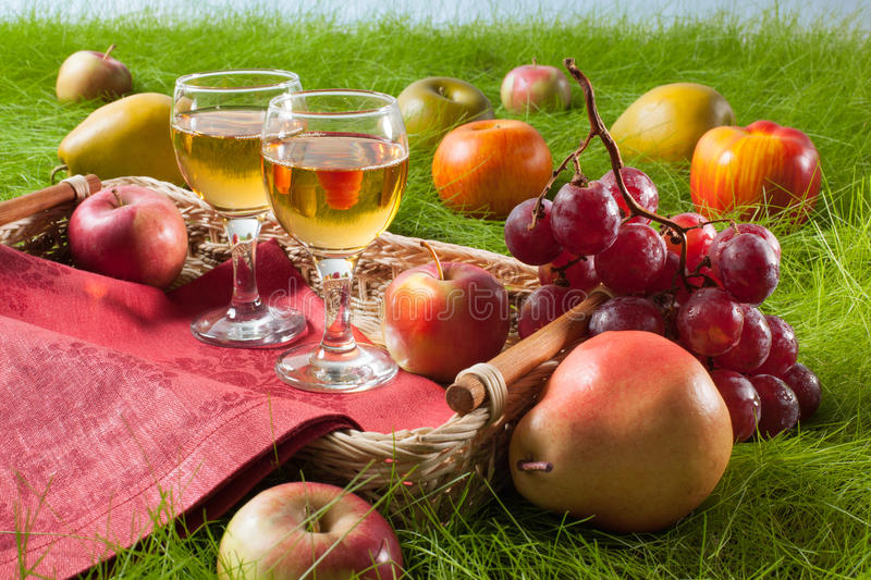 Summer picnic scene with fruiits and vine on grass. Summer picnic scene with fruits and vine on grass stock image