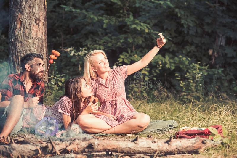 Summer picnic in woods. Smiling blond girl taking selfie in forest or park. Cheerful friends posing with sausages for royalty free stock photography