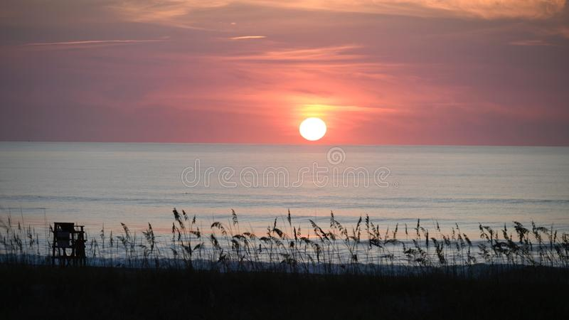 Rising Sun Over Sea Oats. This is a Summer picture of the rising Sun Over sea oats on a beach on the Atlantic Ocean located in Cocoa Beach, Florida in Brevard stock photography