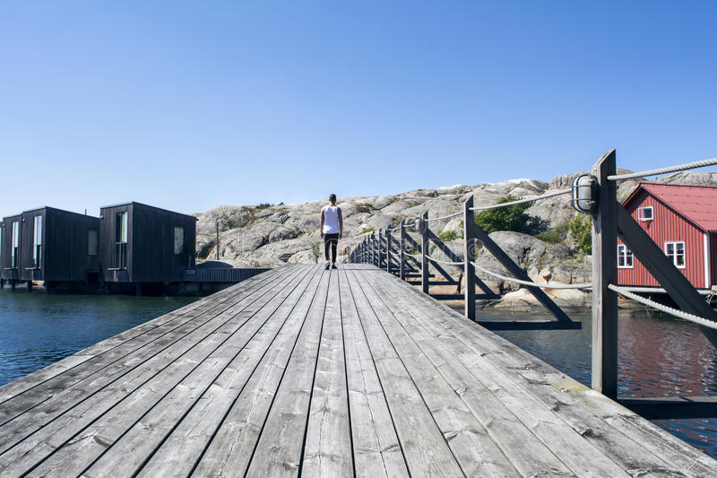 Summer at the pier. Deep perspective of a man walking on a jetty a beautiful summer day stock images