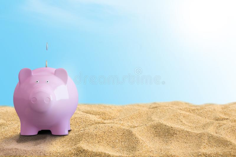 Summer piggy bank on the beach Travel money concept stock images