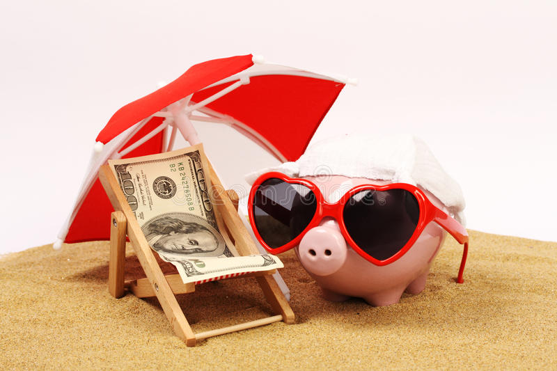 Summer piggy bank with heart sunglasses standing on sand under red and white sunshade next to beach chair with towel from stock photo