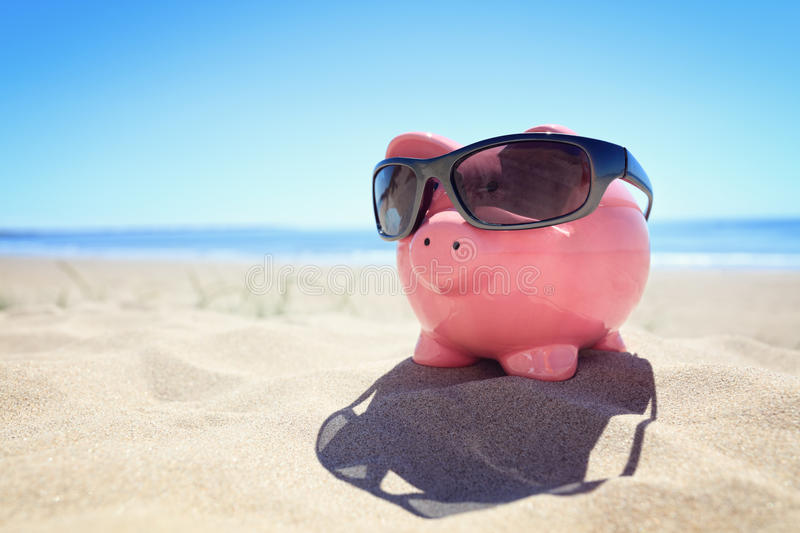 Summer piggy bank with sunglasses on the beach royalty free stock photography