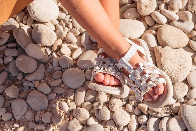 Summer white Shoes for kids, Children`s slippers, beach fashion for baby, Colorful of Sandals shoes and stones, holiday. Summer pink Shoes for kids, Children`s royalty free stock photography