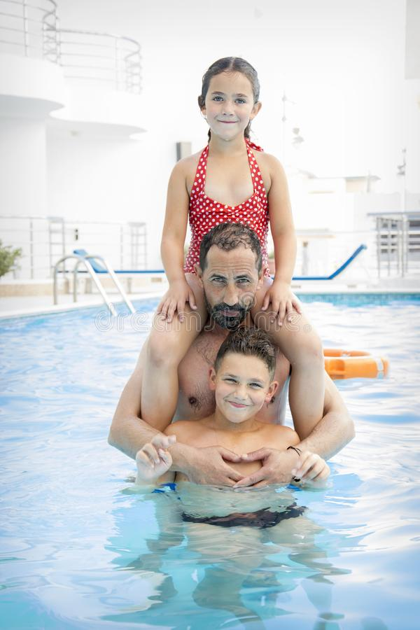 In the summer in the pool, dad with children plays in the pool royalty free stock photo
