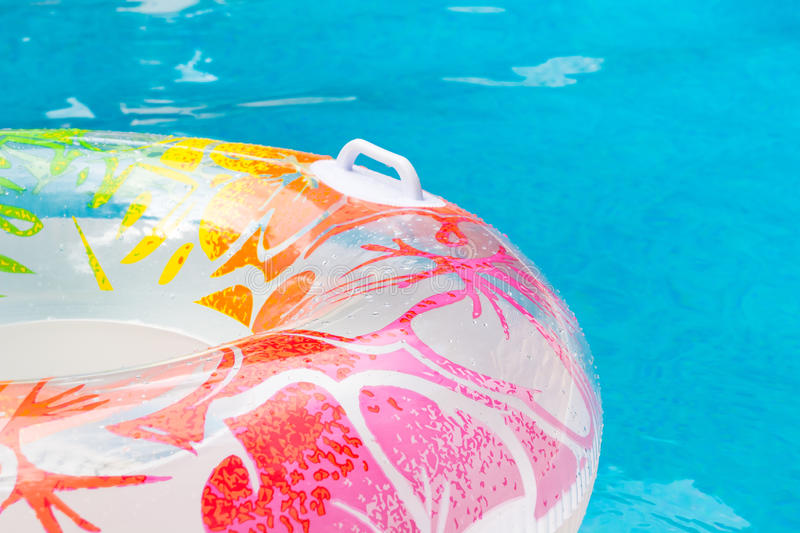 Summer pool dream. Multicolored swim ring floating in a blue swimming summer pool, dream, dreaming on summer days stock images