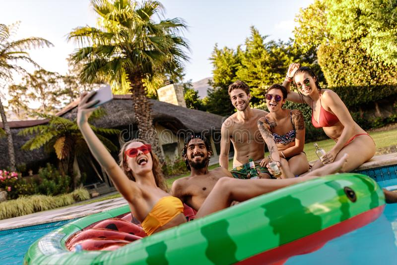 Summer pool party selfie. Crazy people enjoying summer by the swimming pool and taking selfie. Woman sitting on inflatable mattress taking selfie with friends at stock images