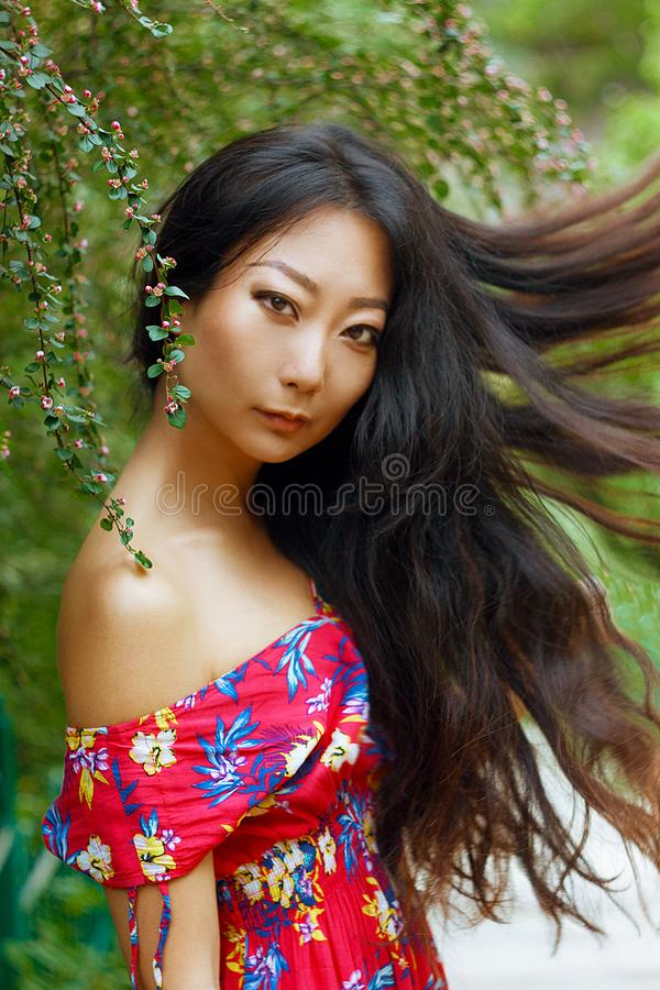 Summer portrait of beautiful Asian woman with long hair on green background. Summer portrait of beautiful Asian woman with long dark hair on green background stock photos