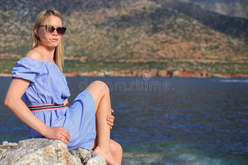 Summer portrait of beautiful girl in sunglasses who is sitting near the sea and mountains royalty free stock photography