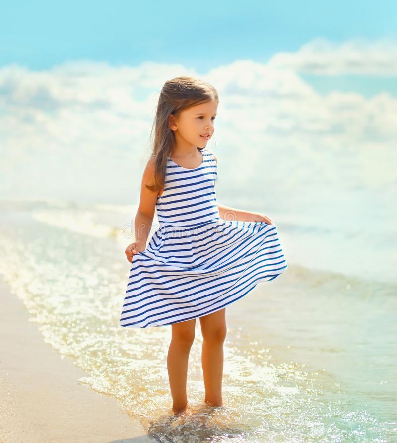 Summer portrait beautiful little girl child in striped dress walking on beach near sea royalty free stock photography